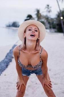 Szczęśliwa młoda europejska kobieta w leopard top bikini jean szorty i klasyczny biały kapelusz na tropikalnej egzotycznej plaży uśmiechnięty pozuje zabawę zabawna dziewczyna na wakacjach podróżować