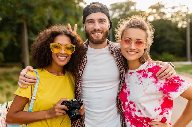 Szczęśliwa młoda firma emocjonalnych uśmiechniętych przyjaciół spaceru w parku z aparatem fotograficznym, mężczyzny i kobiety, bawiące się razem