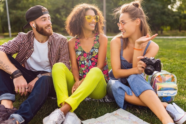 Szczęśliwa młoda firma przyjaciół siedzących w parku, mężczyzny i kobiet, którzy razem bawią się, kolorowy styl mody hipster lato, podróżowanie z aparatem, rozmowa, uśmiechanie się