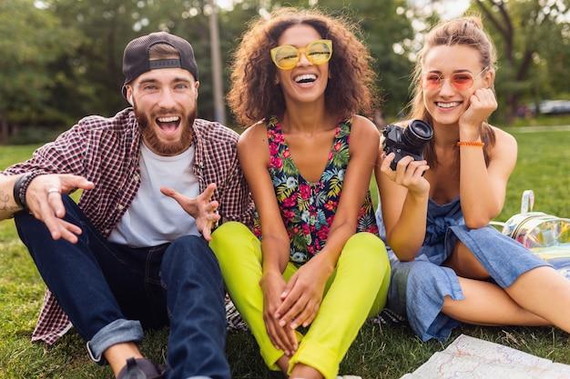 Szczęśliwa młoda firma przyjaciół siedzących w parku, mężczyzny i kobiet, którzy razem bawią się, podróżują z aparatem,