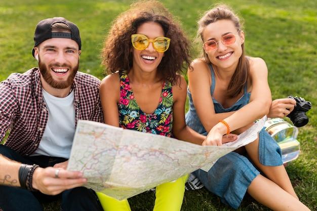Szczęśliwa młoda firma przyjaciół siedzących w parku, podróżujących, patrząc na mapę zwiedzania, mężczyzna i kobiety bawiące się razem