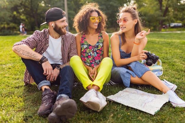 Szczęśliwa młoda firma przyjaciół siedzących w parku podróżujących patrząc na mapie zwiedzanie, mężczyzna i kobiety bawiące się razem, kolorowy styl mody hipster lato, robienie zdjęć w aparacie, rozmowa, uśmiechanie się