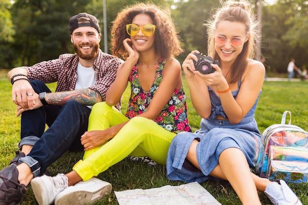 Szczęśliwa młoda firma przyjaciół siedzi w parku, mężczyzna i kobiety razem bawią się, podróżują z aparatem, śmiejąc się szczerze