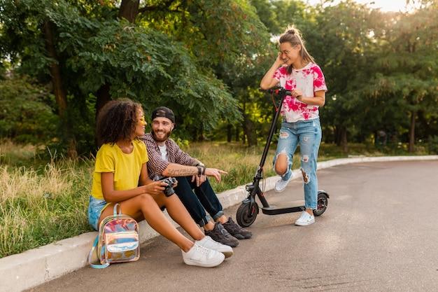 Szczęśliwa młoda firma rozmawiających uśmiechniętych przyjaciół siedzących w parku, mężczyzny i kobiety, spędzając razem czas