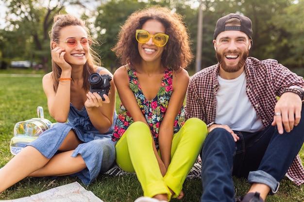 Szczęśliwa młoda firma rozmawiających uśmiechniętych przyjaciół siedzących w parku, mężczyzny i kobiety, wspólnej zabawy, podróżowanie z aparatem