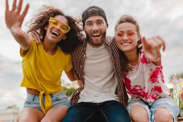 Szczęśliwa młoda firma uśmiechniętych przyjaciół podekscytowanych w parku