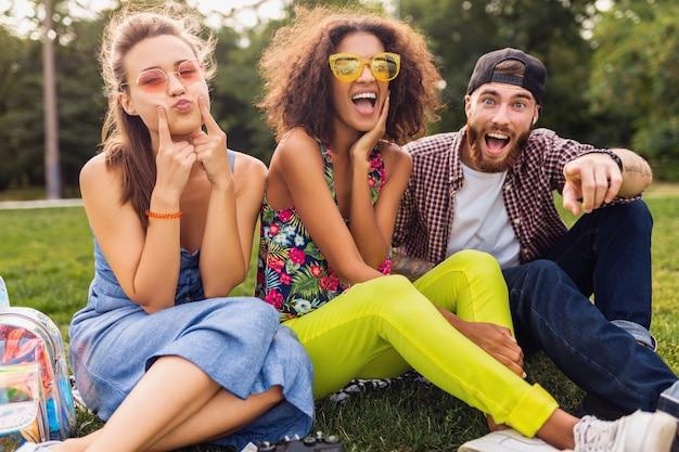 Szczęśliwa młoda firma uśmiechniętych przyjaciół siedzących w parku na trawie, mężczyzny i kobiet, którzy razem bawią się, podróżują, szalony zabawny wyraz twarzy