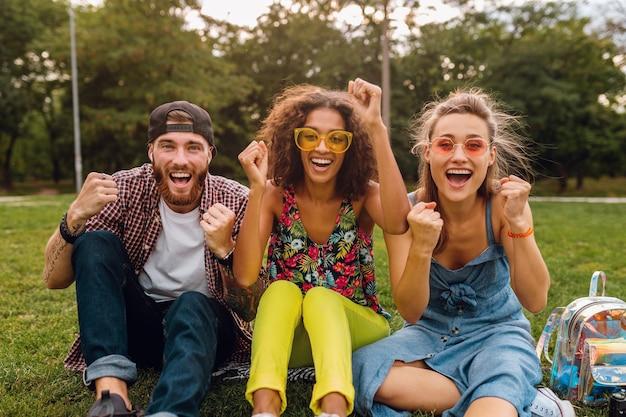 Szczęśliwa młoda firma uśmiechniętych przyjaciół siedzących w parku na trawie, mężczyzny i kobiety, bawiące się razem