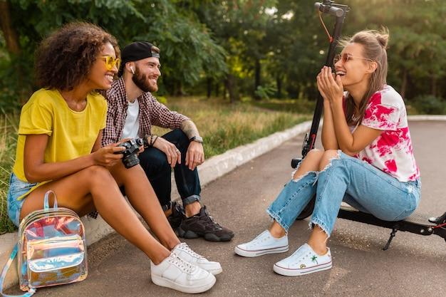 Szczęśliwa młoda firma uśmiechniętych przyjaciół siedzących w parku na trawie z hulajnogą elektryczną, mężczyzna i kobiety, bawiące się razem