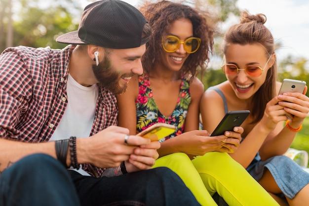 Szczęśliwa młoda firma uśmiechniętych przyjaciół siedzących w parku przy użyciu smartfonów, mężczyzny i kobiety, bawiące się razem