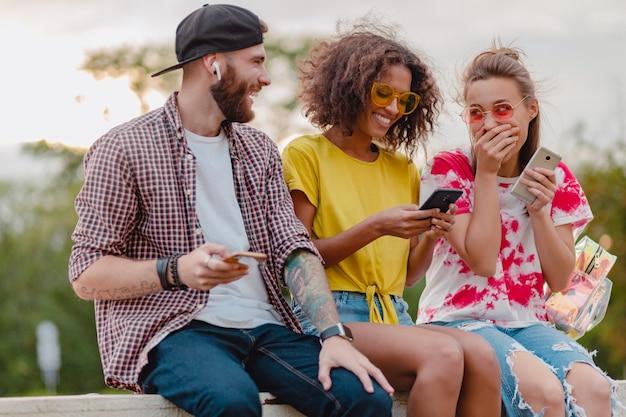 Szczęśliwa młoda firma uśmiechniętych przyjaciół siedzących w parku przy użyciu smartfonów, mężczyzny i kobiety, zabawy