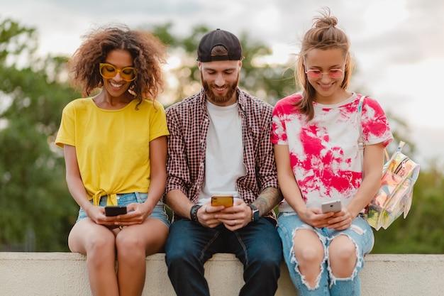 Szczęśliwa młoda firma uśmiechniętych przyjaciół siedzi w parku za pomocą smartfonów