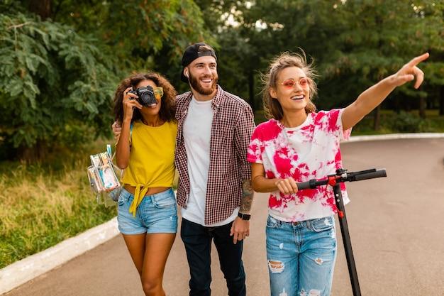 Szczęśliwa młoda firma uśmiechniętych przyjaciół spacerujących w parku z hulajnogą elektryczną, mężczyzny i kobiety bawiące się razem, kolorowy letni styl mody hipster, podróżujący z aparatem, rozmawiający, uśmiechnięty