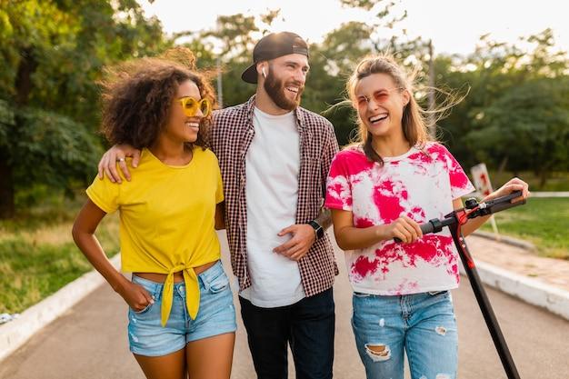 Szczęśliwa młoda firma uśmiechniętych przyjaciół spacerujących w parku z hulajnogą elektryczną, mężczyzny i kobiety, bawiące się razem