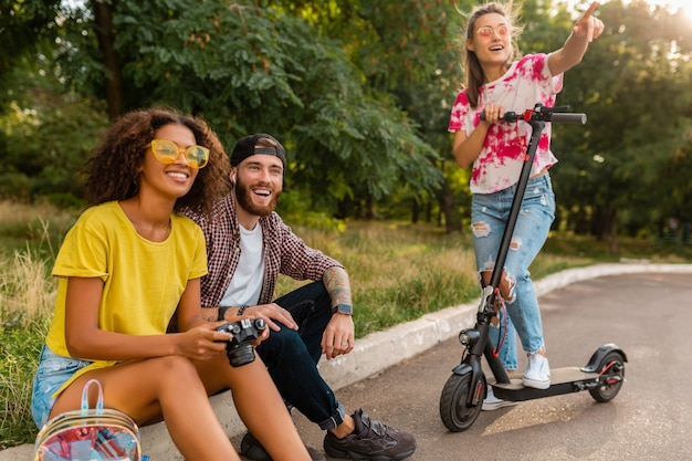 Szczęśliwa młoda firma uśmiechniętych przyjaciół w parku, mężczyzny i kobiety, spędzając czas razem na zwiedzaniu z aparatem