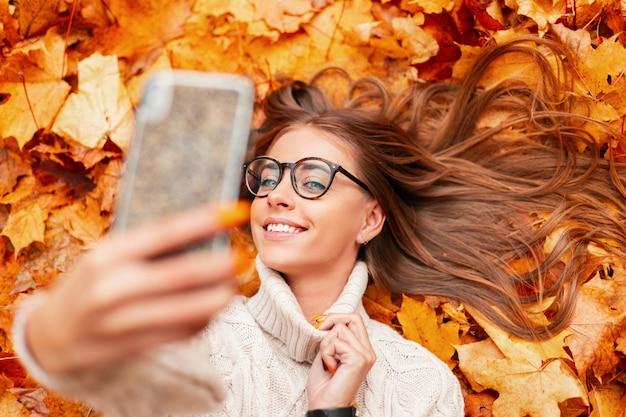 Szczęśliwa młoda hipster kobieta sprawia, że selfie w telefonie. atrakcyjna, wesoła modelka w stylowych okularach w białym swetrze z dzianiny vintage fotografuje siebie leżącą w pomarańczowych liściach. widok z góry.