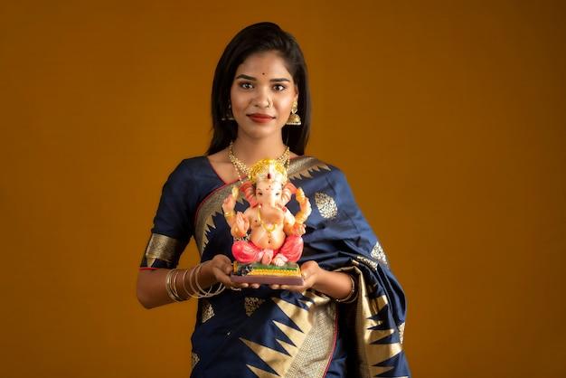 Szczęśliwa Młoda Indianka Pozuje Z Posągiem Ganesha Z Okazji Ganesh Festival Premium Zdjęcia