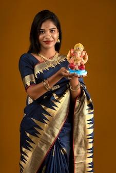 Szczęśliwa młoda indianka pozuje z posągiem ganesha z okazji ganesh festival