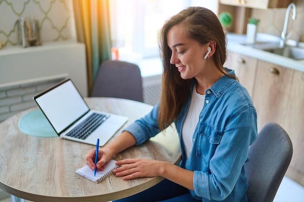 Szczęśliwa młoda inteligentna tysiącletnia kobieta robi notatkę za pomocą pióra w notatniku i używa laptopa z otwartym białym pustym wyświetlaczem do edukacji online w obszarze roboczym. makieta komputerowa do reklamy na stronie internetowej