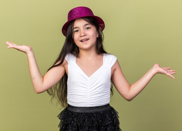 Szczęśliwa młoda kaukaska dziewczyna w fioletowym kapeluszu imprezowym trzymająca otwarte ręce odizolowana na oliwkowozielonej ścianie z miejscem na kopię
