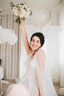 Szczęśliwa młoda kaukaska panna młoda siedzi jej ślubnego bukiet i trzyma