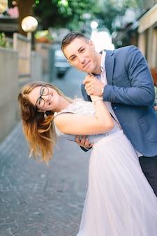 Szczęśliwa młoda kaukaska para w błękitnych ślubów ubraniach chodzi na ulicach stary grodzki sirmione, włochy