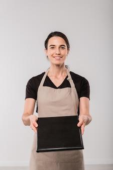 Szczęśliwa młoda kelnerka kawiarni w fartuchu daje menu w czarnej skórzanej okładce stojąc przed kamerą
