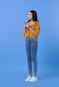 Szczęśliwa młoda kobieta azjatyckich dobry patrząc za pomocą telefonu komórkowego na czacie na białym tle na fioletowo.