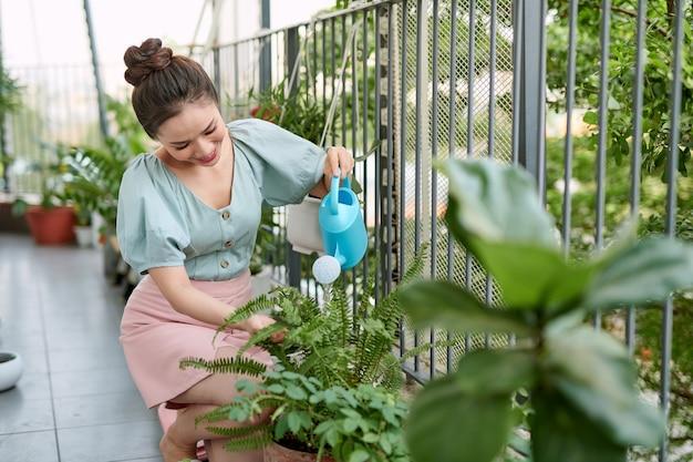 Szczęśliwa młoda kobieta azjatyckich gospodyni podlewanie kwiatów na balkonie