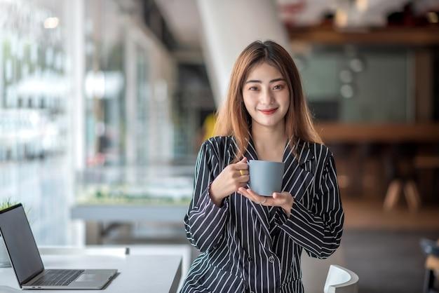 Szczęśliwa młoda kobieta azjatyckich picia kawy przy stole z laptopem w kawiarni.