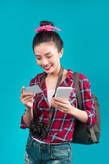 Szczęśliwa młoda kobieta azjatyckich posiadania karty kredytowej i smartphone stojący na niebiesko.
