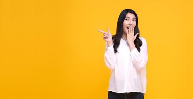 Szczęśliwa młoda kobieta azjatyckich, stojąca z jej palcem wskazującym na białym tle na żółty sztandar z miejsca na kopię.