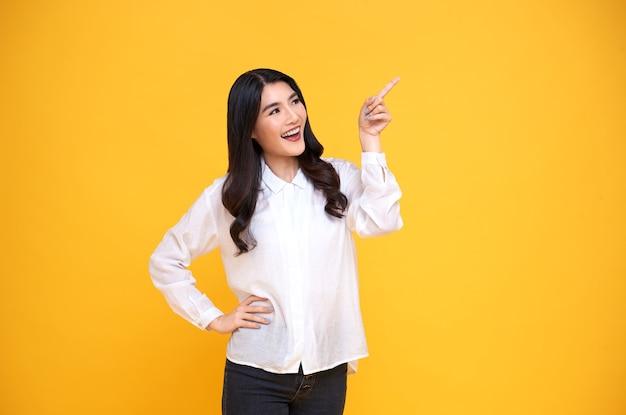 Szczęśliwa młoda kobieta azjatyckich, stojąca z jej palcem wskazującym na białym tle na żółtym tle transparentu z miejsca na kopię.