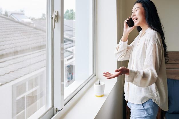 Szczęśliwa młoda kobieta azji śmiejąc się i rozmawiając przez telefon z przyjacielem, stojąc w oknie mieszkania