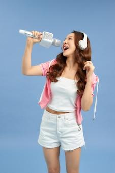 Szczęśliwa młoda kobieta azji śpiewa z mikrofonem śpiewać i słuchawki na niebieskim tle.
