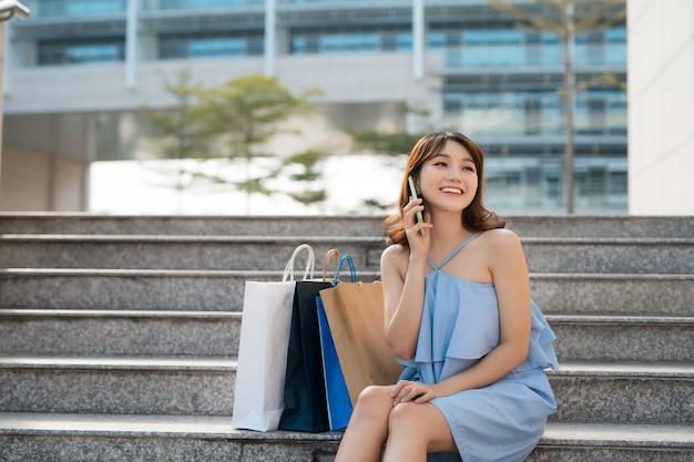 Szczęśliwa młoda kobieta azji z torby na zakupy dzwoniąc na telefon komórkowy i siedząc na schodach.