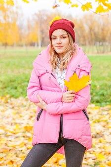 Szczęśliwa młoda kobieta bawi się spadającymi żółtymi liśćmi w pięknym jesiennym parku na spacerach natury. nastoletnia dziewczyna trzyma jesień pomarańczowy liść klonowy.