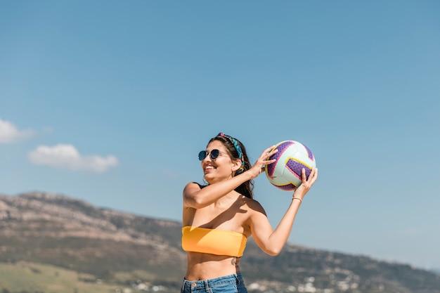 Szczęśliwa młoda kobieta bawić się z piłką