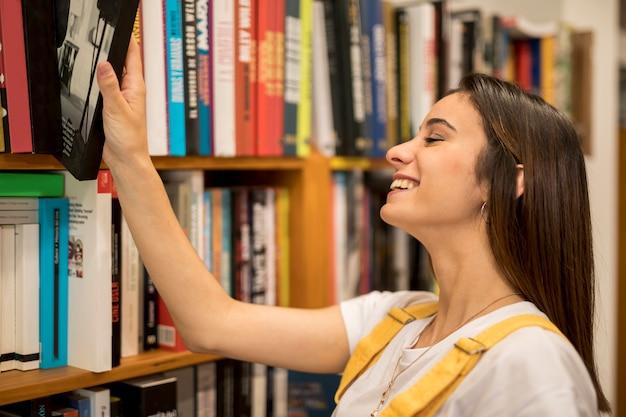 Szczęśliwa młoda kobieta bierze książkę od półka na książki