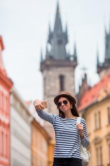 Szczęśliwa młoda kobieta bierze selfie tła sławnemu kasztelowi w europejskim mieście. kaukaski turysta spacerujący po opuszczonych ulicach europy. ciepłe lato wczesnym rankiem w pradze, republika czeska