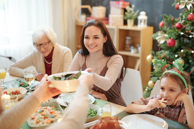 Szczęśliwa młoda kobieta, biorąc miskę z sałatką domowej roboty z rąk męża na świąteczny stół