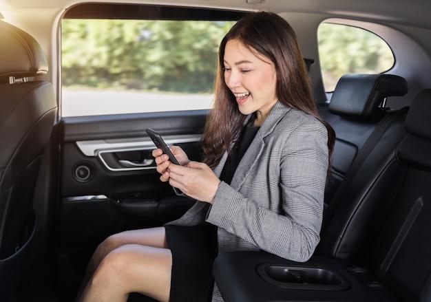 Szczęśliwa młoda kobieta biznesu za pomocą smartfona siedząc na tylnym siedzeniu samochodu