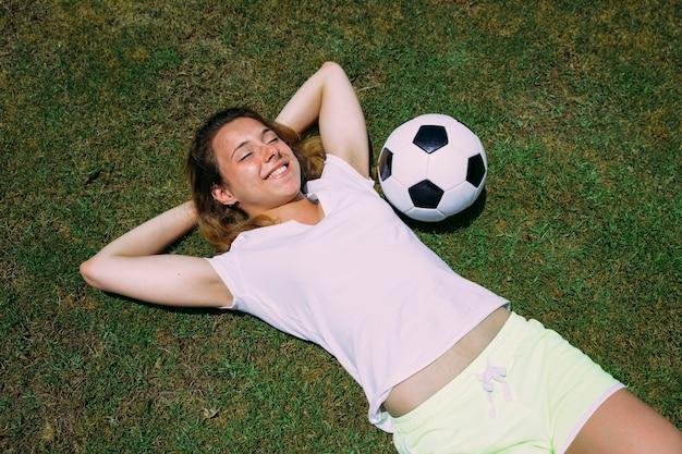 Szczęśliwa młoda kobieta blisko piłki na trawie