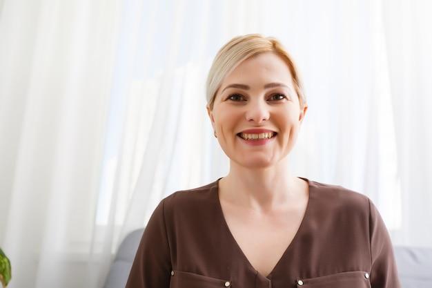 Szczęśliwa młoda kobieta blogerka zgłaszająca nauczyciel siedzi w domowym biurze patrzeć na kamerę podczas rozmowy kwalifikacyjnej online podczas czatu wideo nagrywanie rozmowy konferencyjnej vlog nauczanie na seminarium internetowym w aplikacji, widok z kamery internetowej