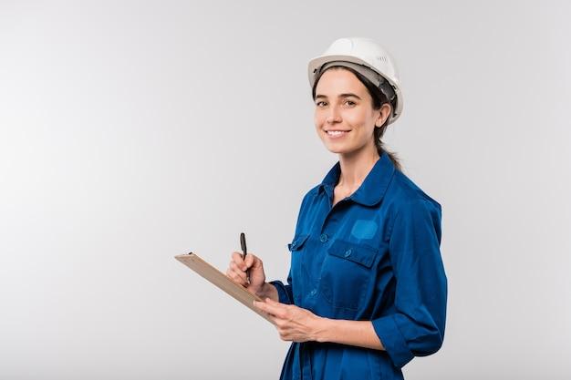 Szczęśliwa młoda kobieta budowniczy w niebieskiej odzieży roboczej i kasku robiącym notatki w dokumencie, stojąc w izolacji