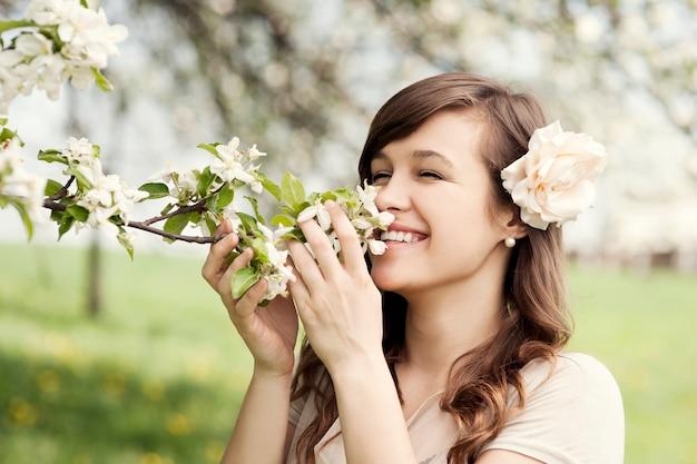 Szczęśliwa młoda kobieta, ciesząc się zapachem kwiatów