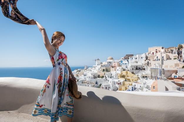 Szczęśliwa młoda kobieta cieszy się widoku oia wioskę w santorini wyspie, grecja.