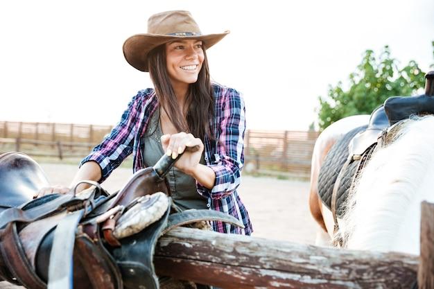 Szczęśliwa młoda kobieta cowgirl w kapeluszu uśmiecha się i przygotowuje siodło do jazdy konnej
