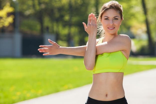 Szczęśliwa młoda kobieta ćwiczy outdoors