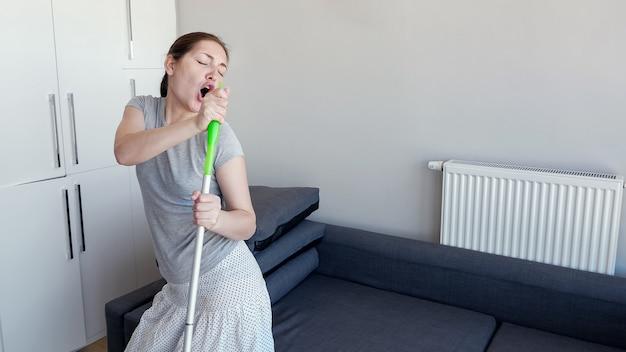 Szczęśliwa młoda kobieta czyści swój dom. myje podłogę za pomocą mopa, śpiewa piosenkę i tańczy w swoim nowoczesnym mieszkaniu, kopiując przestrzeń